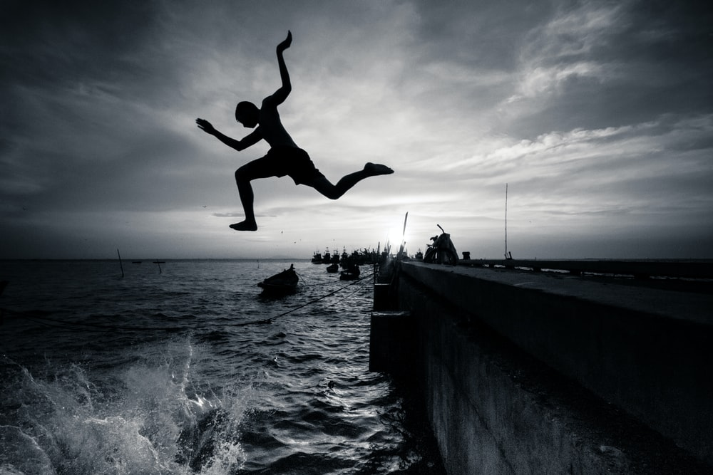 silhouette photography of man jumping on sea