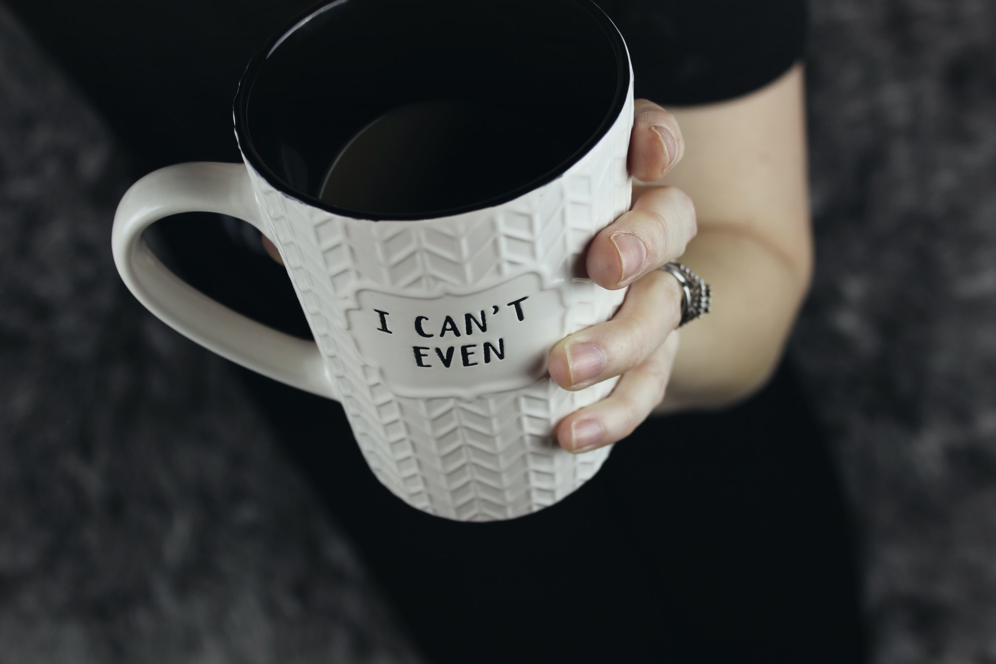 "For those mornings when getting out of bed seems like the most difficult task in the world, this white coffee mug with herringbone pattern and texture tells it like it is: ""I can't even..."" held in a woman's hand with large wedding ring against a dark background."