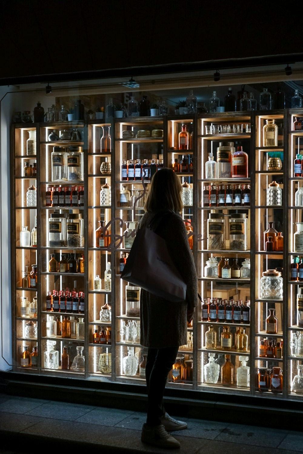 woman standing beside liquor stone