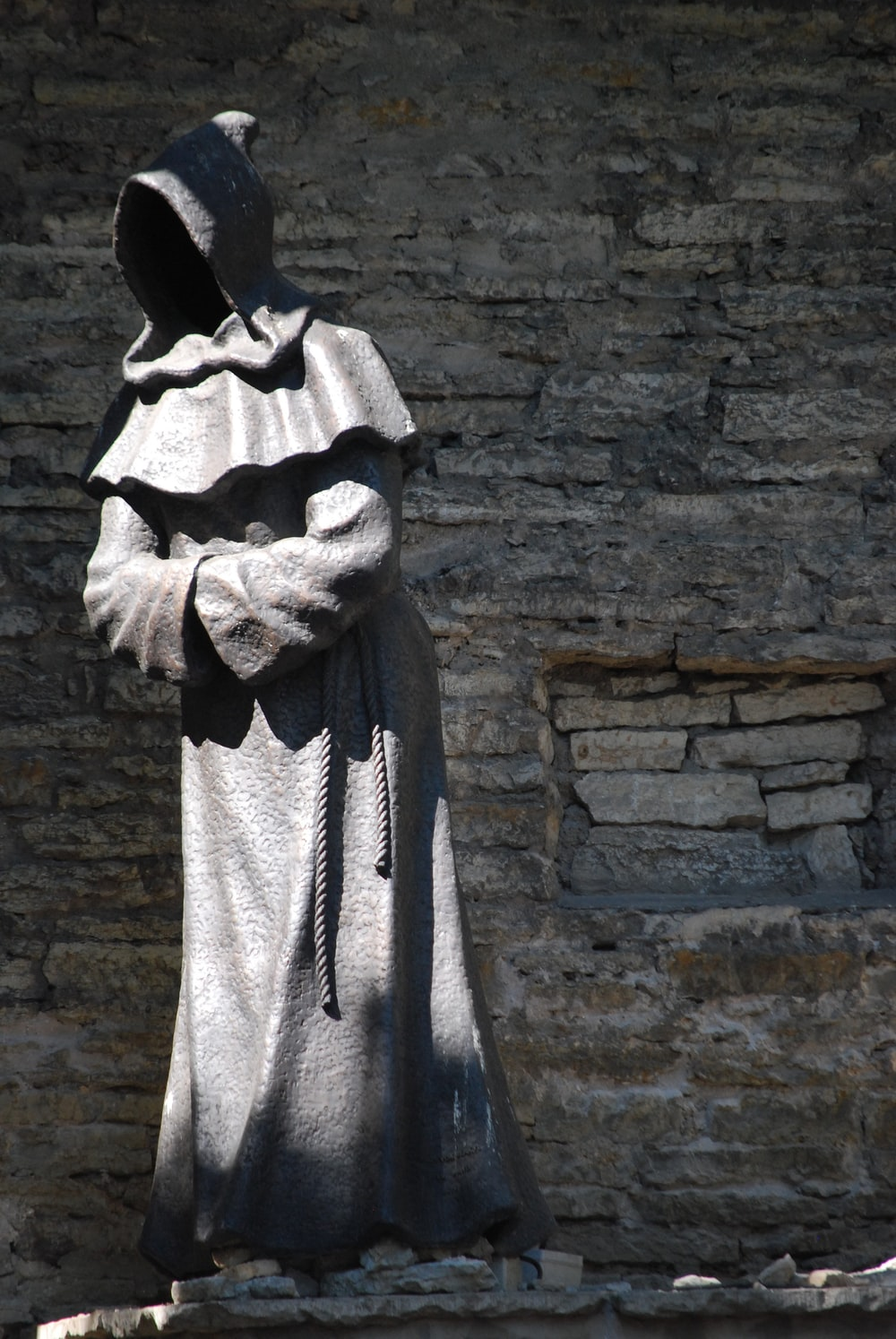 person wearing hooded dress statue