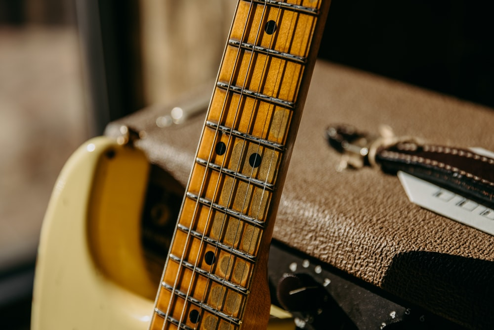 selective focus photography of brown guitar leaning on speaker