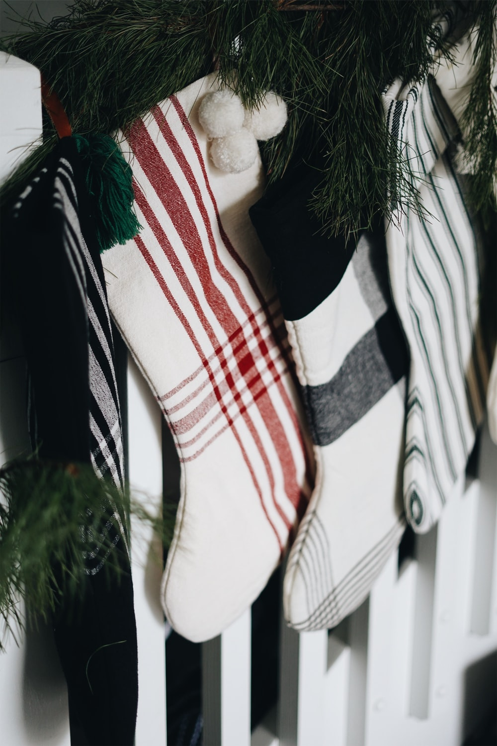 white and red Christmas stocking hanging near pine tree