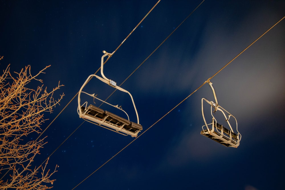 two white cable cars under blue and white sky