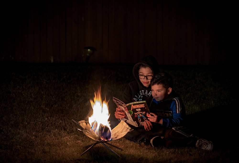 woman wearing eyeglasses sitting near boy reading Avengers comic book beside bonfire during night time