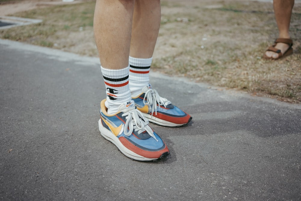 person wearing multicolored Nike shoes standing