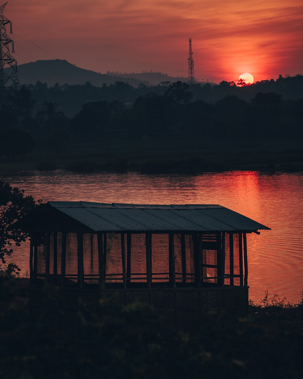 shed near water during sunset