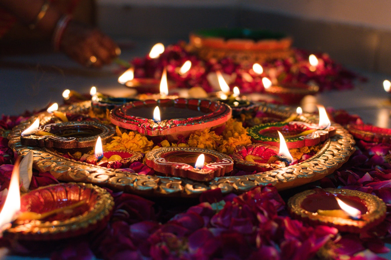 Earthern lamps (diyas) placed over rose petals makes for an excellent karwa chauth tips