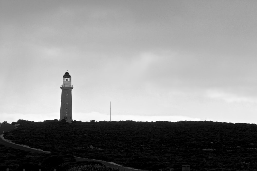 lighthouse grayscale photo