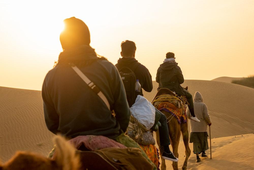 three men riding on camels