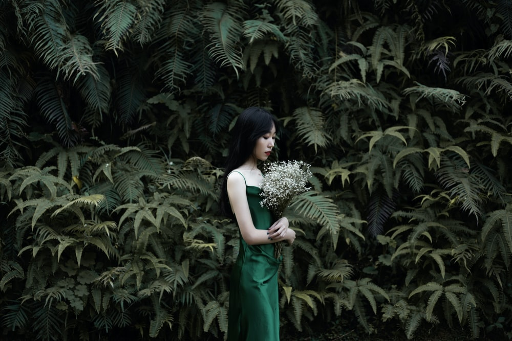 woman standing beside flowers during daytime
