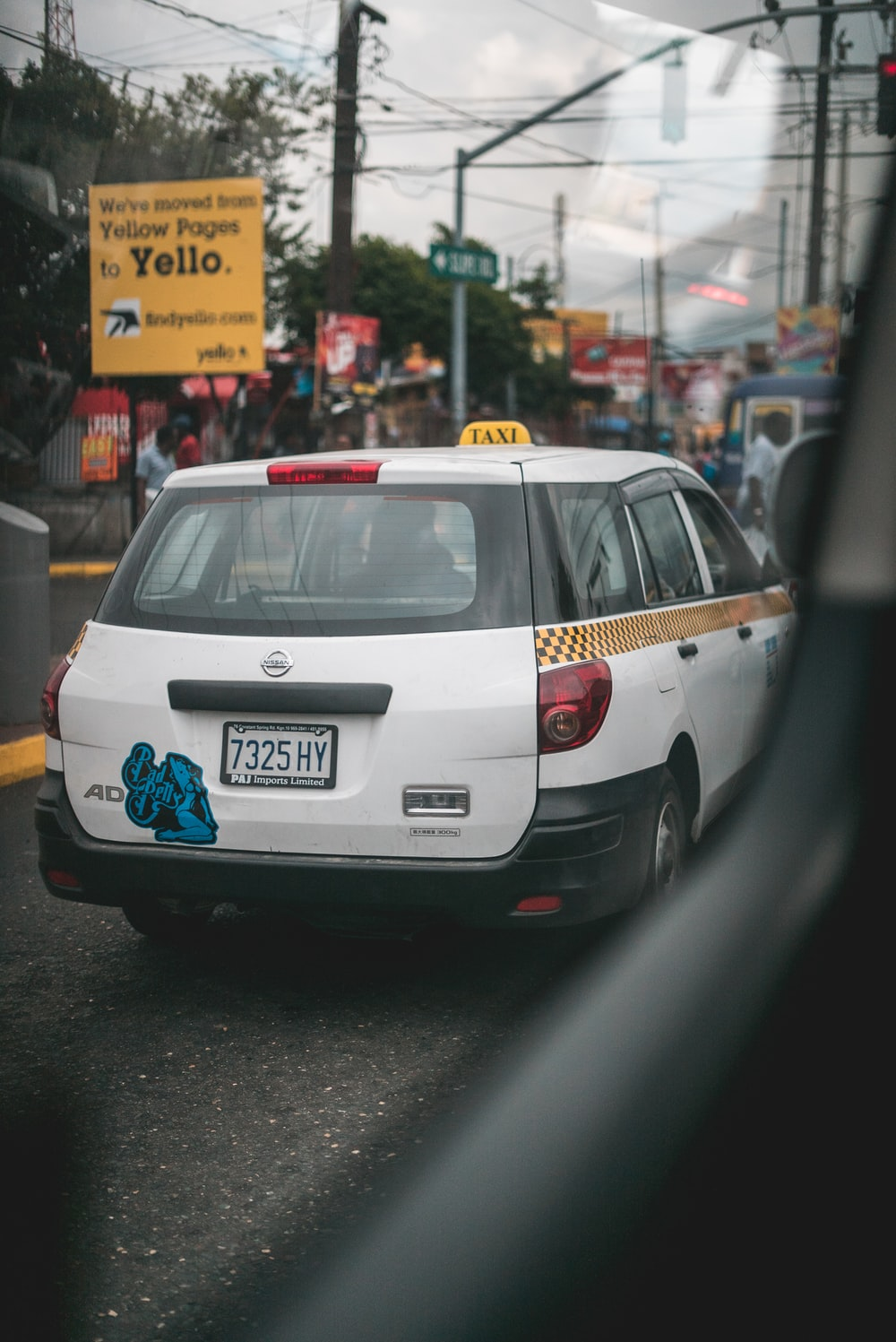 white Nissan vehicle on road