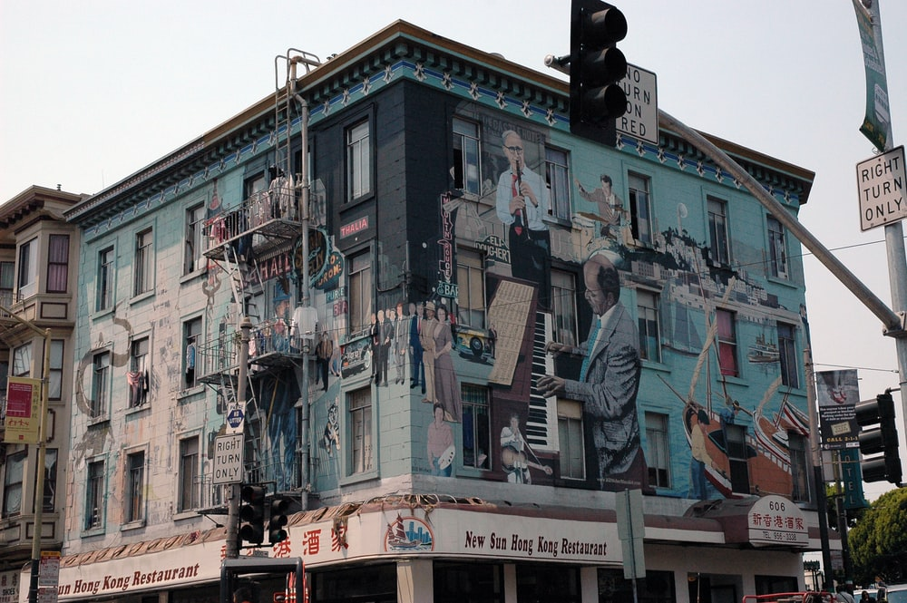 building with murals near traffic light during day