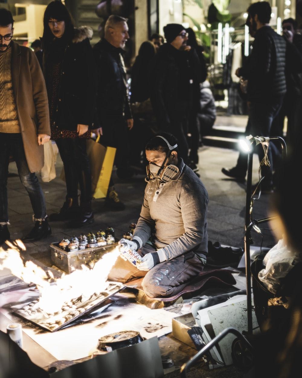 kneeling man torching artwork on canvas near people