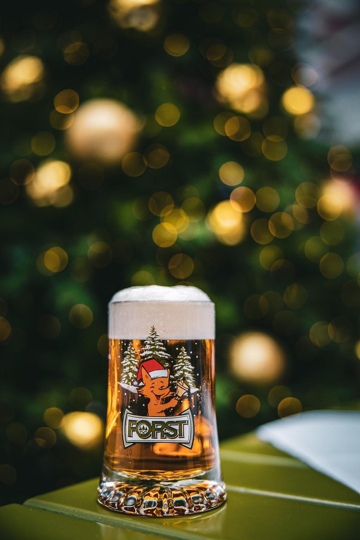 full clear Forst beer mug on green surface