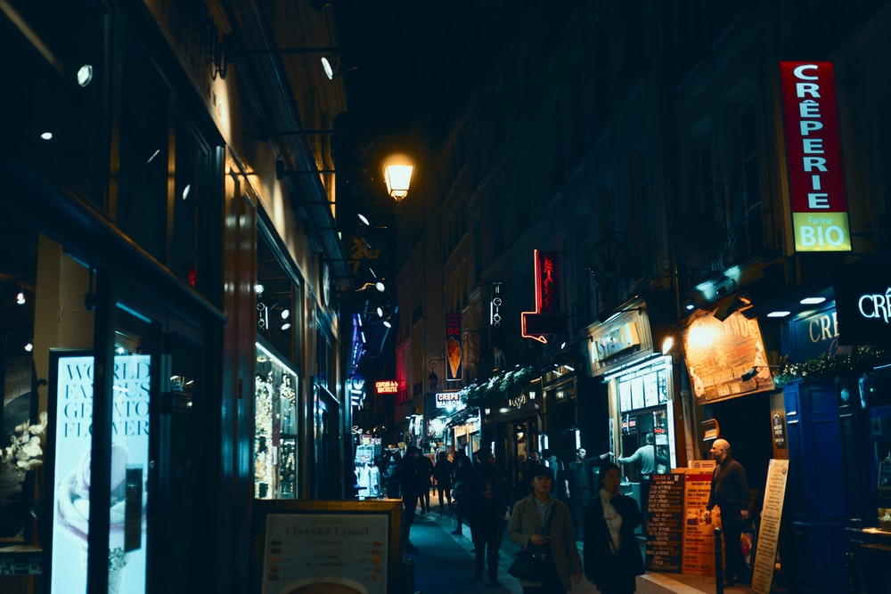 photography of people waking near street during nighttime