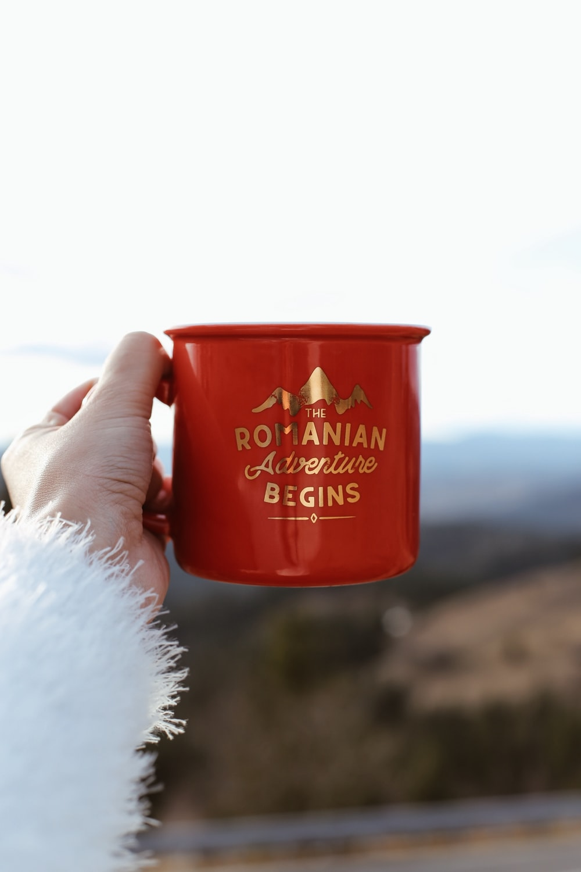 person holding red Romanian Adventure Begins mug