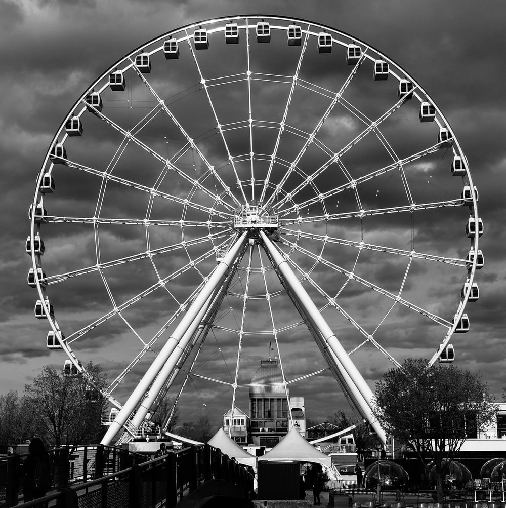 grayscale photography of ferris wheel near building