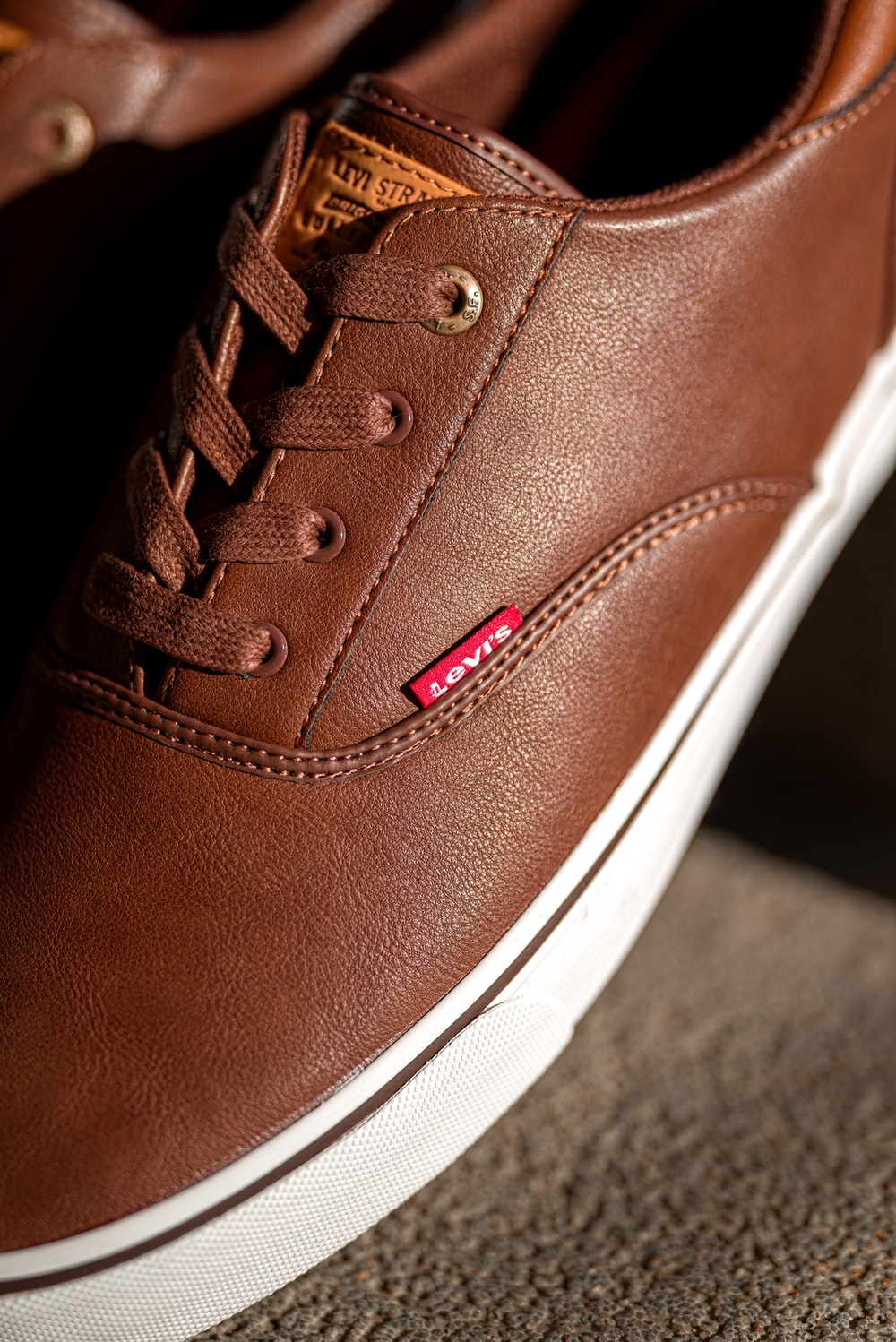 unpaired brown Levi's leather low-top lace-up sneaker