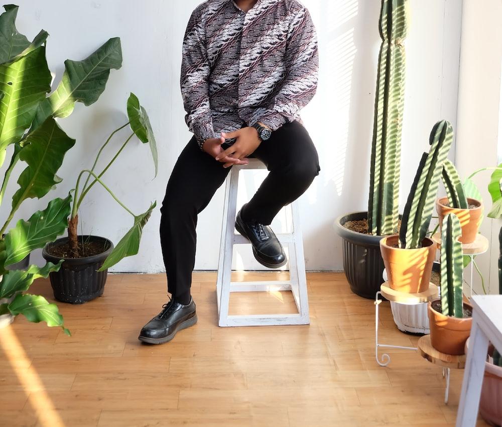 man sitting on white stool beside plants inside building