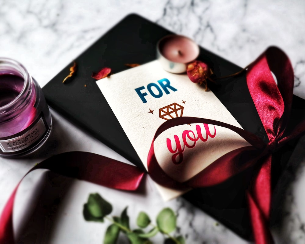 greeting card beside a red ribbon and tealight candle