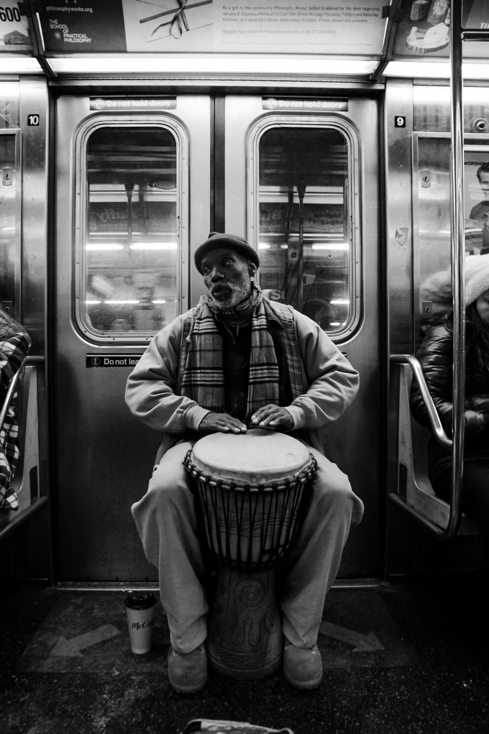 man playing djembe inside the train