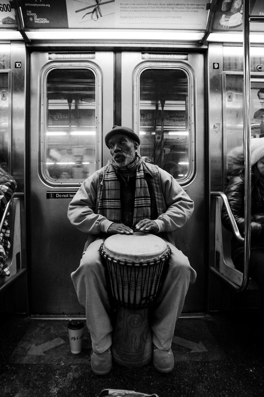 man playing djembe inside the train