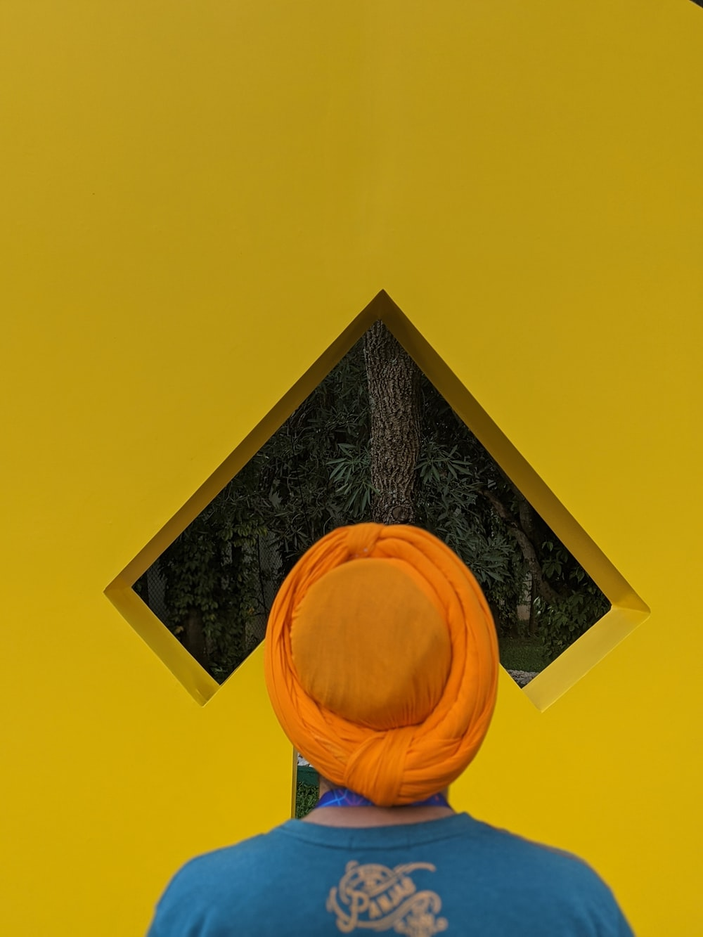 person wearing blue and brown shirt and orange turban hat standing while facing back