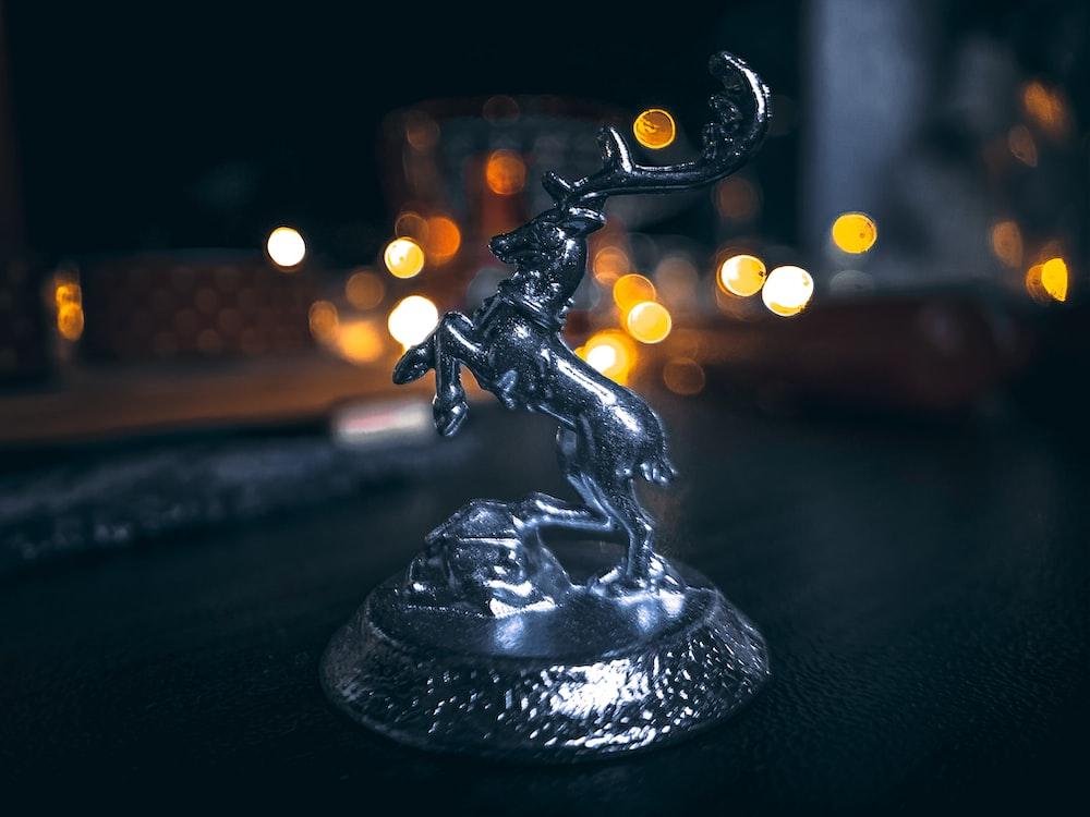 macro photography of gray rearing horse figurine