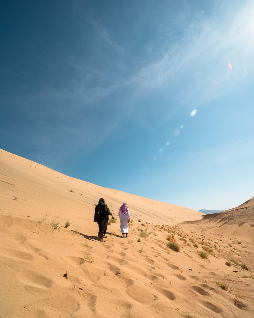 two people walking on desert under blue and white sky