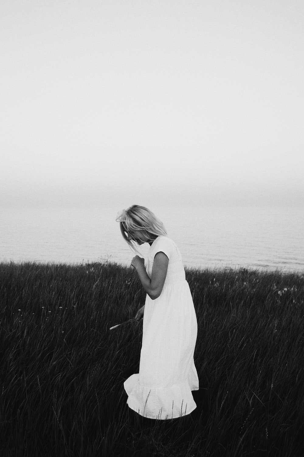grayscale photography of woman wearing dress standing while looking down