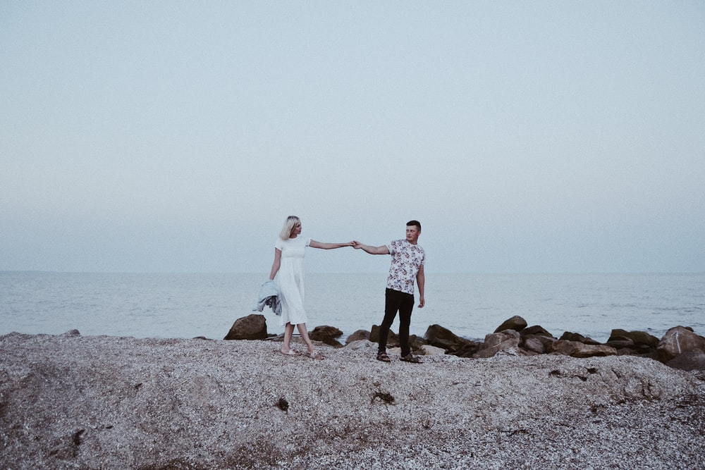 man and woman standing while holding hands together near body of water