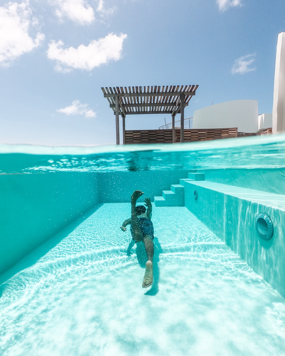 person swimming in rectangular green swimming pool under blue and white sky