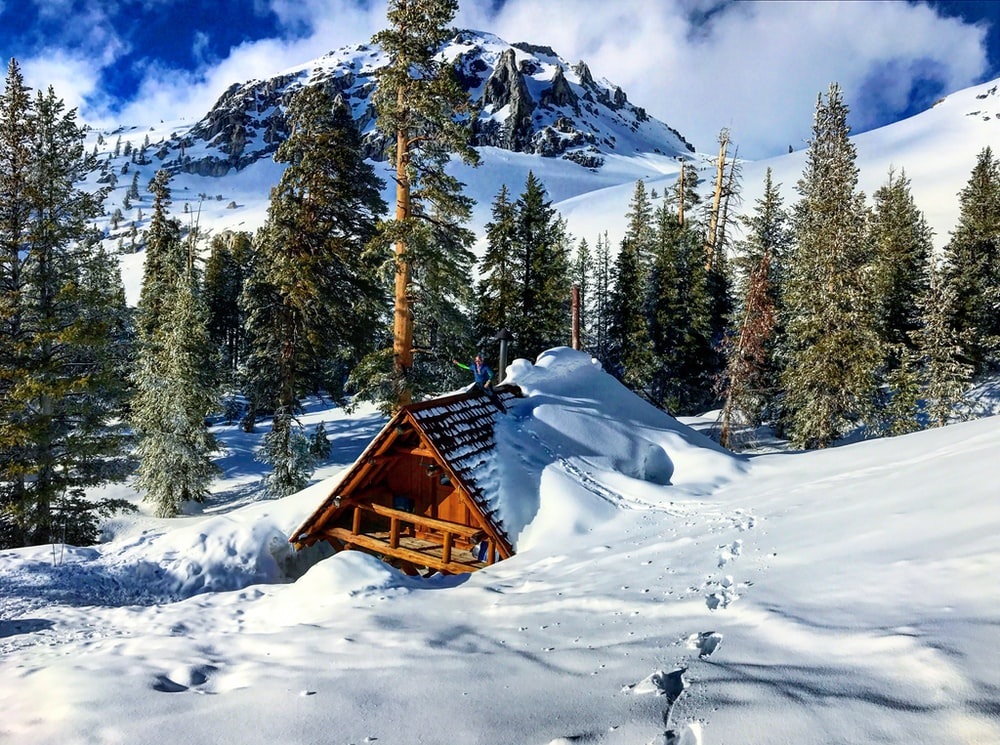 cabin covered with snow on hill