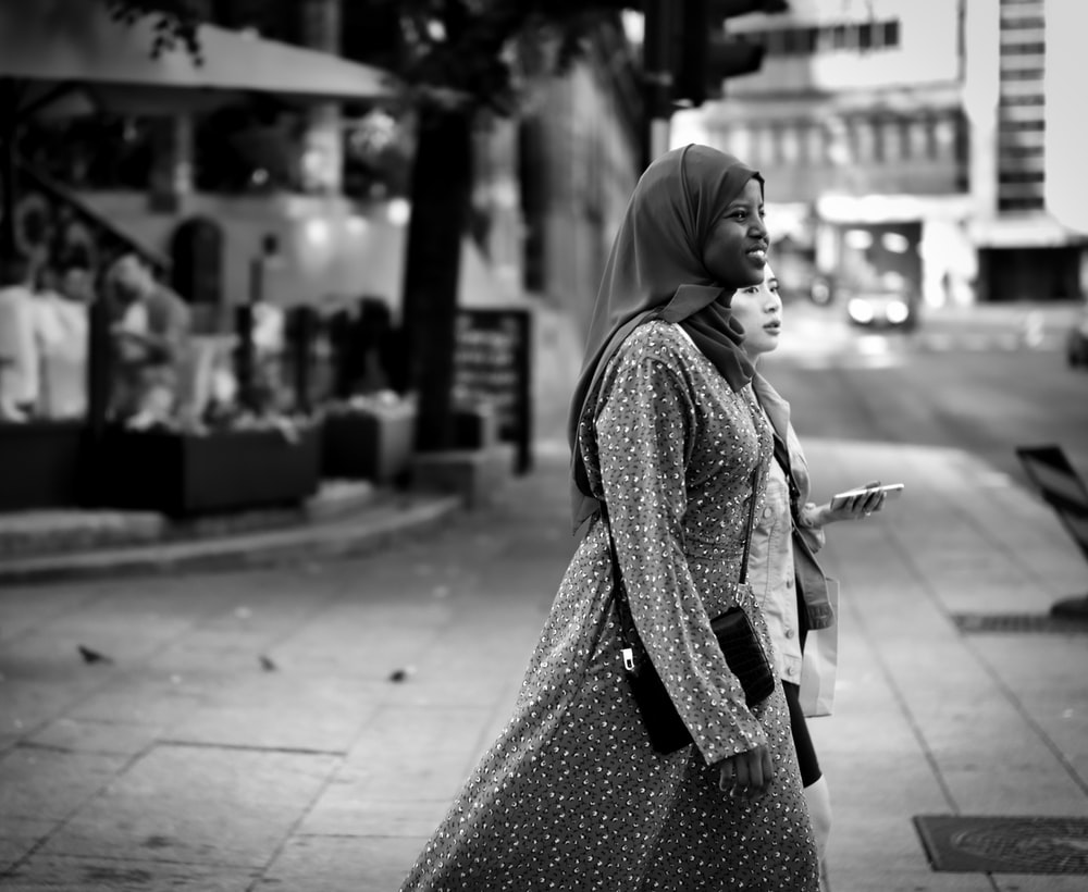 grayscale photography of smiling walking woman