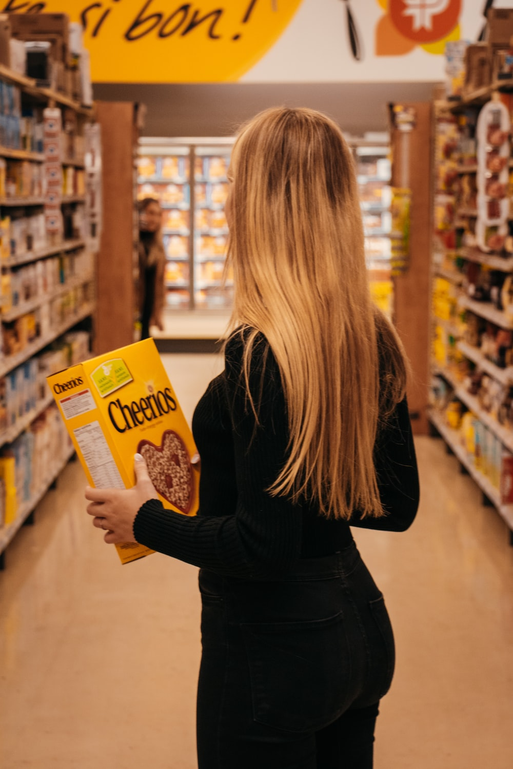 woman wearing black long-sleeved shirt holding Cheerios cereal box standing