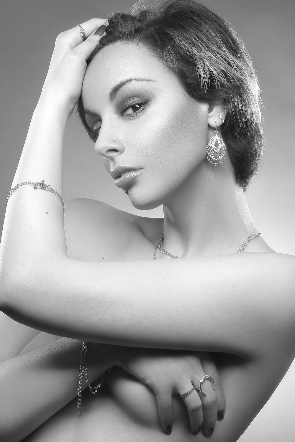 grayscale photography of topless woman covering breast and one hand on hair