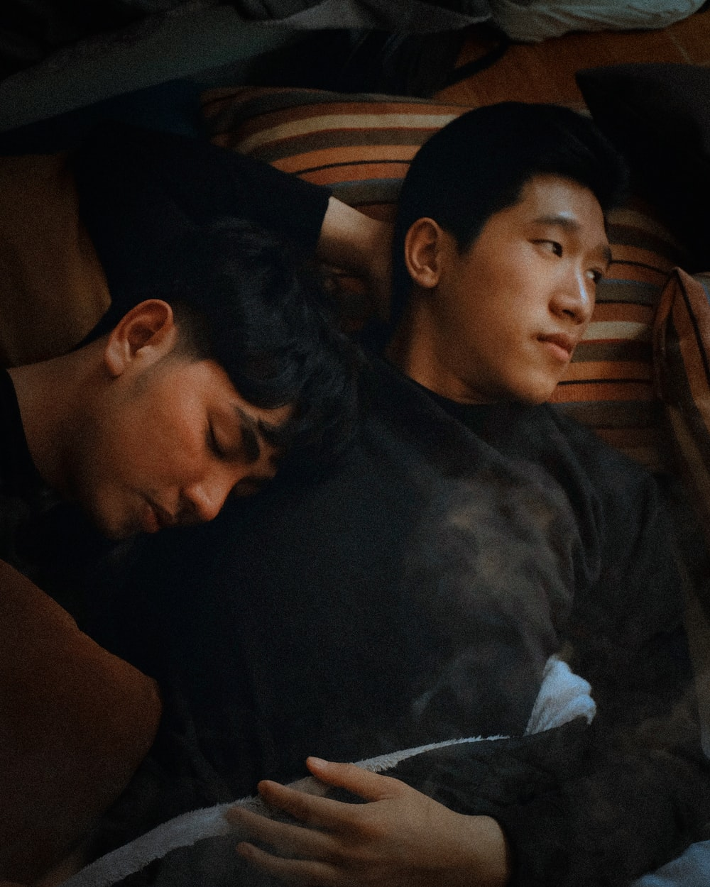 man lying beside man