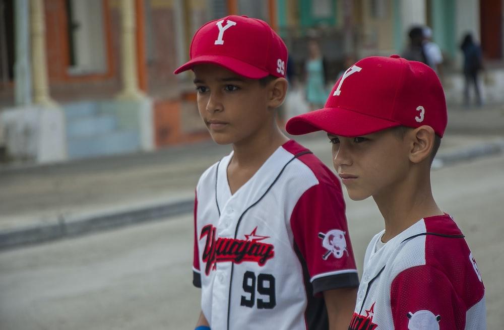 two boys wearing baseball uniform during day