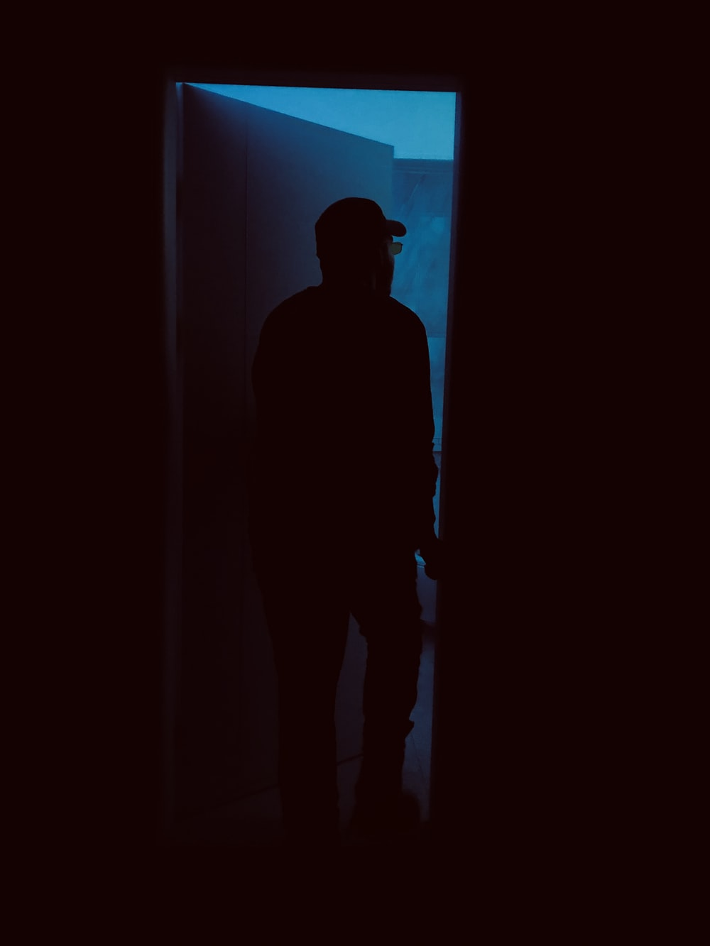 silhouette of person entering door