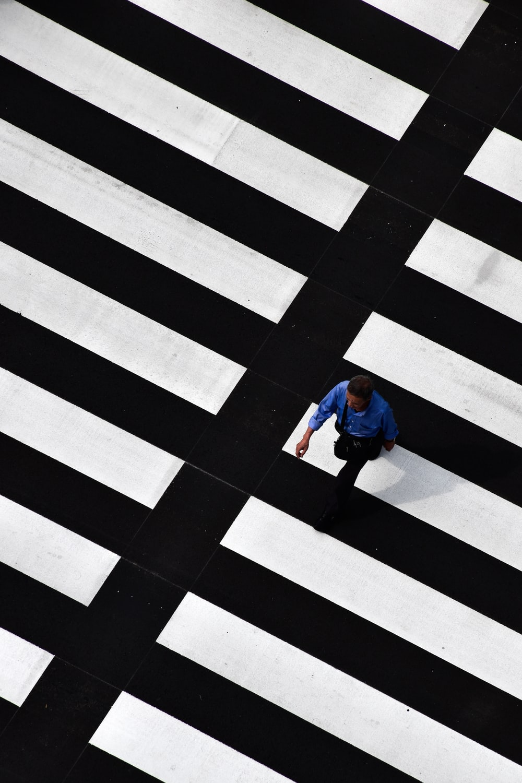 man walking on crosswalk during day