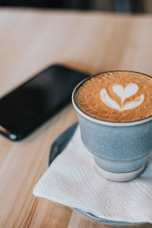 macro photography of cappuccino in mug on a table napkin