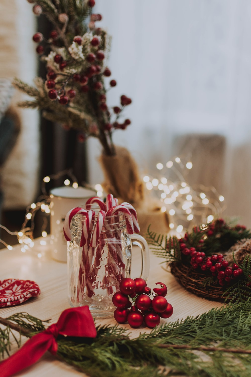 candy cane in clear glass jar near red baubles, lighted string lights, and white mug