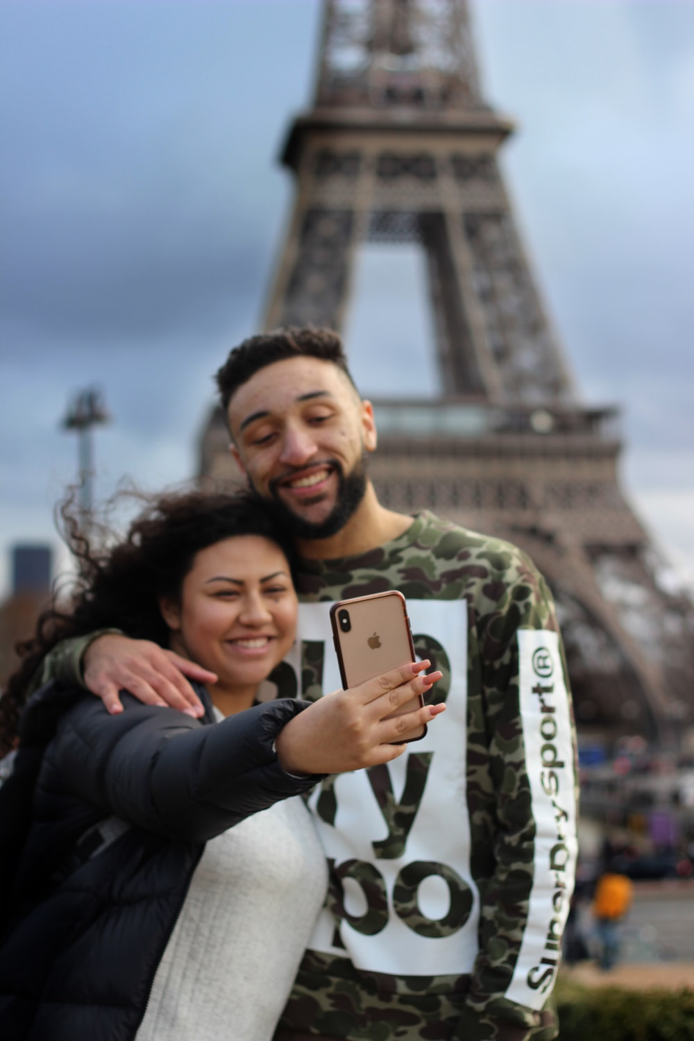 man and woman taking picture near Eiffel Tower in Paris