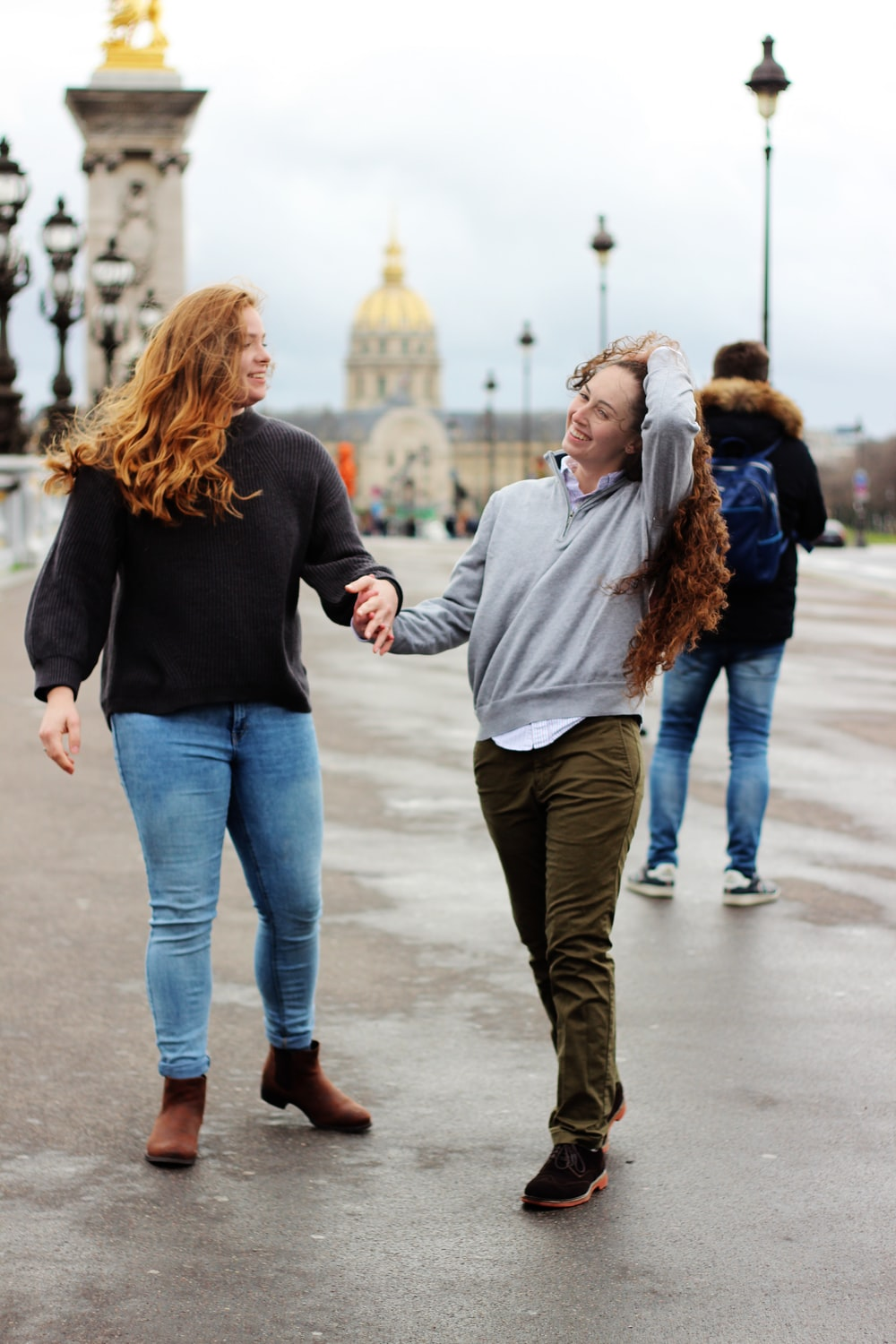 two women holding hands together while walking on road during daytime