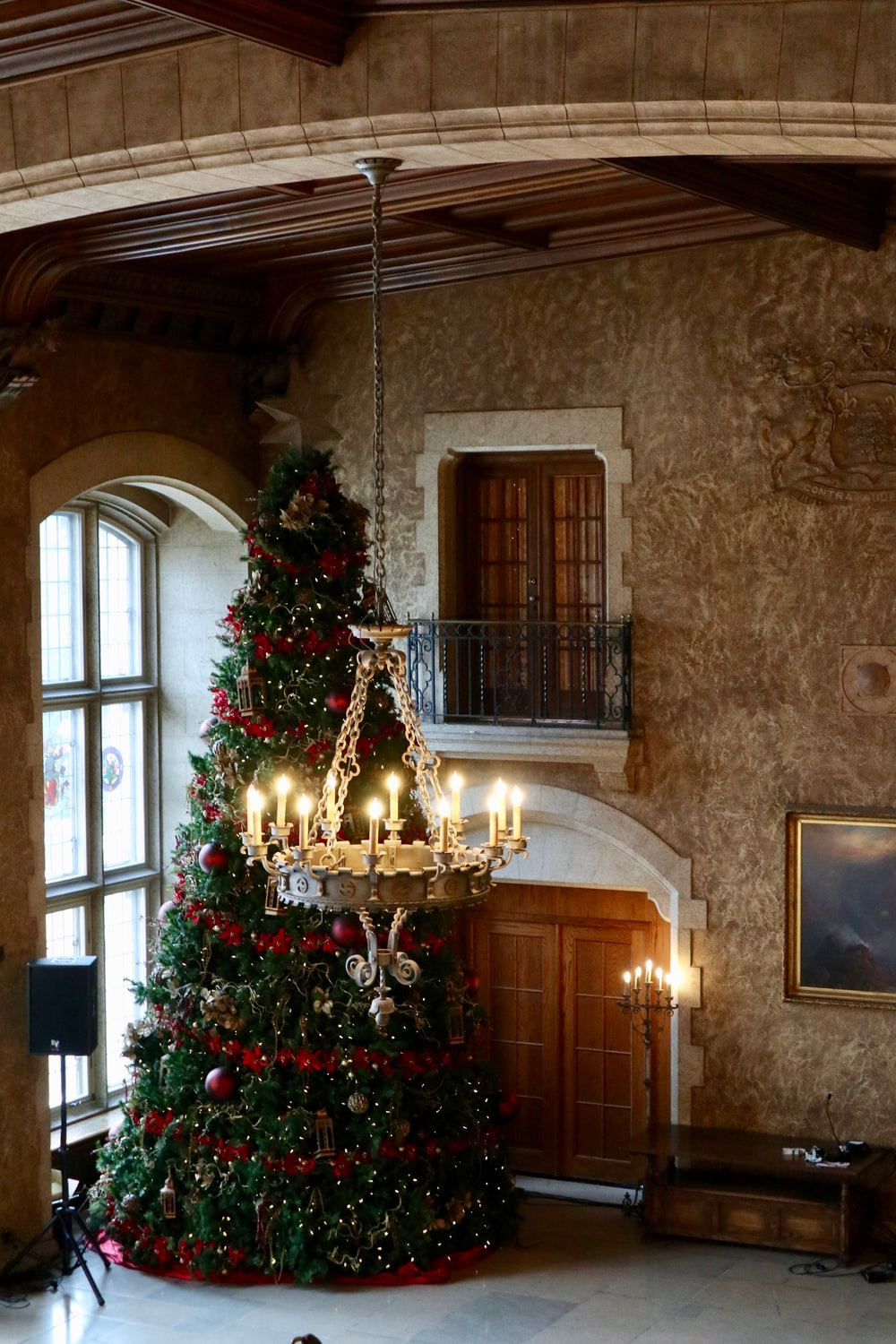 Christmas tree beside closed doors and near chandelier turned on