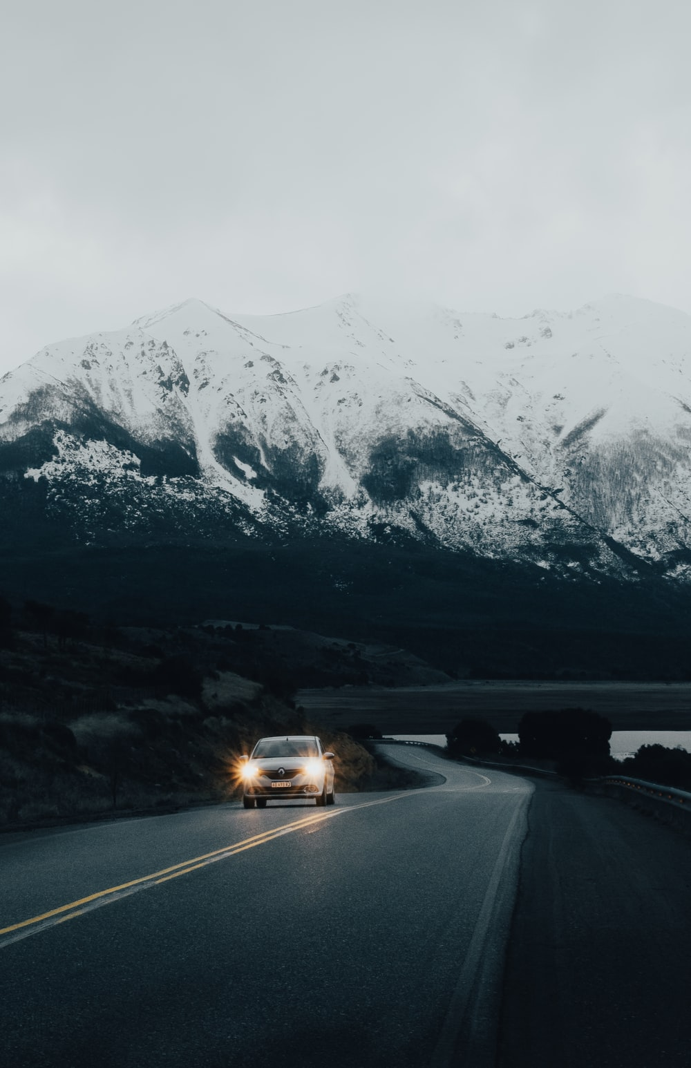 white vehicle on road viewing mountain covered with snow during daytime