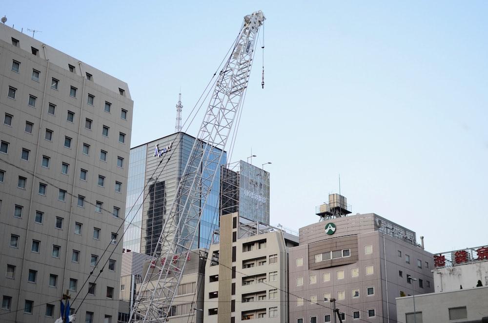 grey metal crane beside buildings during daytime