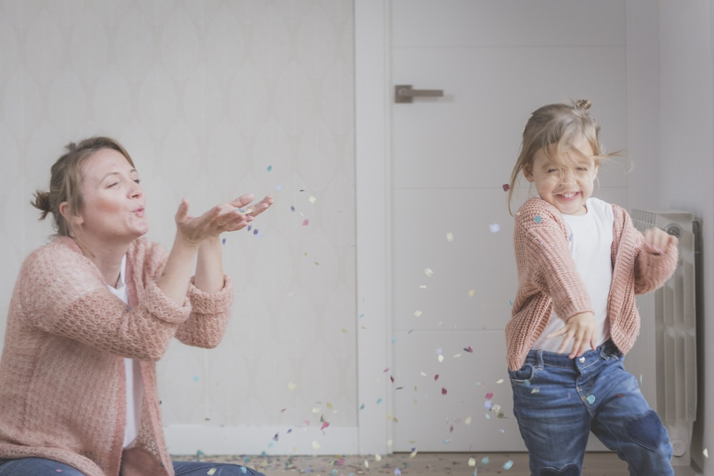 woman and child wearing beige sweater playing with confetti