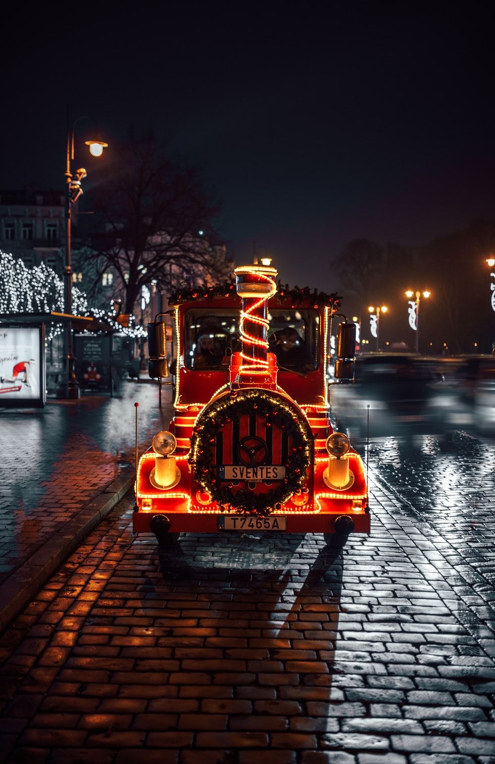 red and black train with lighted string lights during night time
