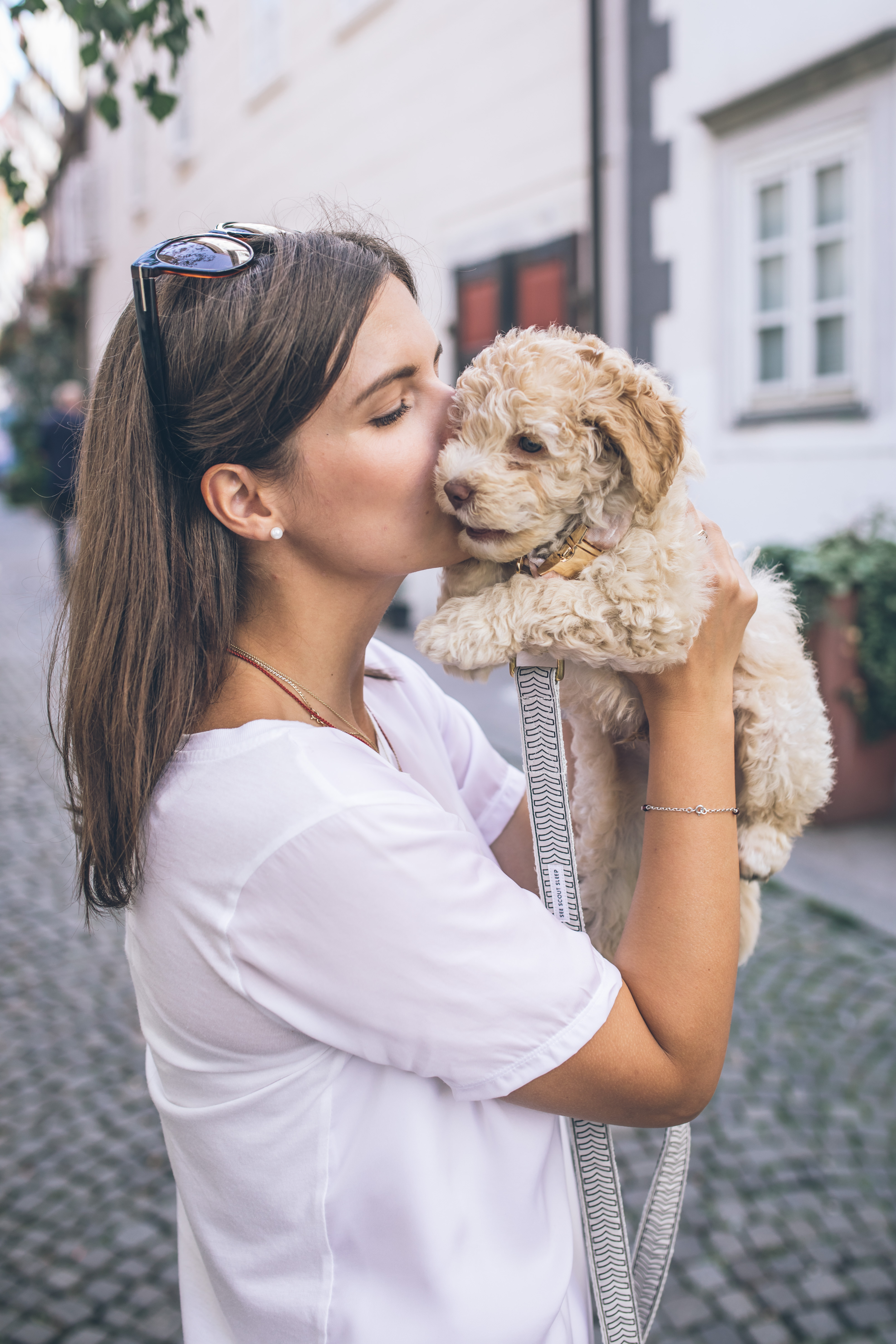 woman kissing a cockapoo puppy